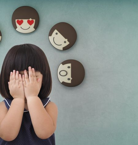 Portrait of a little girl covering her face and 3d rendering of emotion icons