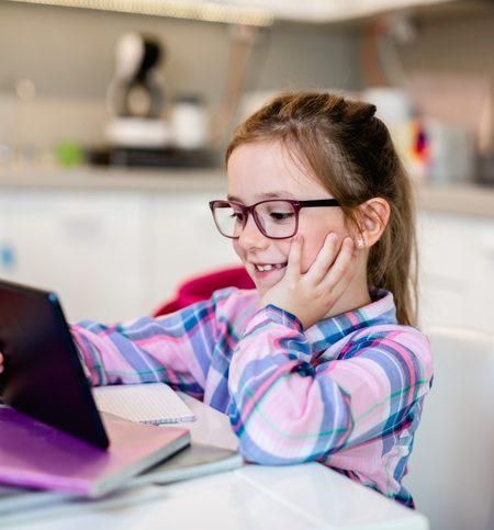 Cute little girl holding tablet while doing her homework.